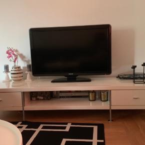 Højglans TV bord - måler ca. 200cm i længden. Købt i Ilva. Brugt i et par år, der er af brugstegn. Sælges - er åben for bud. TV bordet står i Vanløse.