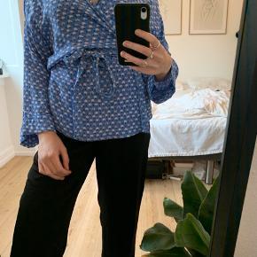 Rigtig fin slå-om bluse med bindebånd i taljen. Blå med svagt lyserøde blomster.