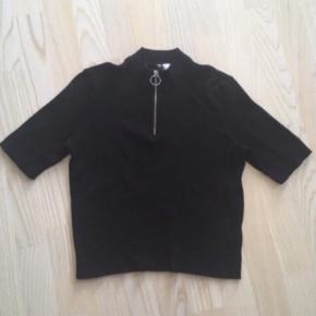 Sort kort t-shirt i lidt tyk rib kvalitet. Med lynlås i hals. Cool til jeans eller nederdel. Str. L men svarer til en M