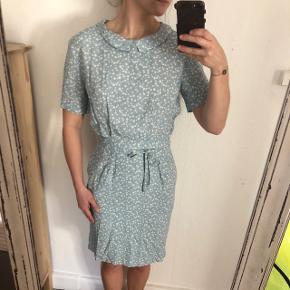 En fin lyseblå Ganni kjole. Den er i god stand. Der mangler en enkelt knap bagpå og der er en mikroskopisk plet på kjolens forside (som kan ses på billedet, kan den ikke ses med det blotte øje).