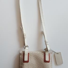 Crossbody/Skuldertaske fra DKNY i stof med skindkanter.  DKNY skuldertaske, ét rum. Farven er beige og rød. Rumlig og i fin stand. Målene er 23x21,5cm