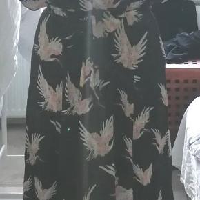 Fin skjortekjole med knaplukning ned til taljen og bindebånd i taljen. Den er sort med traner aftegnet i lyse farver