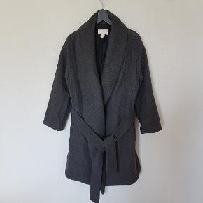 Frakken er i pæn stand. Grå med bindebånd.