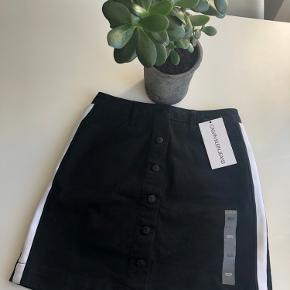 Calvin Klein sort nederdel  m. hvid stribe langs siden og knapper str. 29 🦍  Materiale: 98% Bomuld 2% Elastan  Nederdelens mål:  Længde: 46 cm.  Bredde 53 cm. (målt forneden hvor den er bredest)   Byd gerne kan enten afhentes i Århus C eller sendes på købers regning 📮✉️