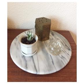 Rund marmor plade. Den har en fod under så den kan rotere. Jeg har brugt den til pyntegenstande, men kan også bruges som bordskåner, som tapasbræt, som ostebræt eller hvad du nu synes :)   Sender gerne med DAO :)