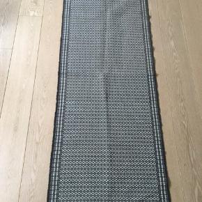 Lækker tæppe/løber i gråsorte og hvide farver. Ikke brugt ret meget. Mål: 70*200 cm. 100 kr. plus porto.