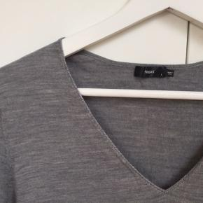 Super let bluse/kjole i ekstra fin og fleksibel merinould fra Filippa K. Gråmelleret med v-hals.   Str hedder large, men den er ikke kæmpe. Måler 77cm midt bag på.  Den hvide top/underkjole på profilen er glat, og passer perfekt under blusekjole her.