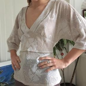 Fin bluse der kan bindes på ryggen og derfor passe de fleste størrelser