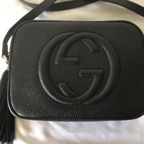 """Gucci Soho Disco Bag Black Leather Klassisk sort Gucci taske.  Brugt få gange, ingen tydelig slid på læderet, men lidt små ridser på guldet på """"tassel"""".  Der er et stort rum med en lille lomme i hver side. Mål: 21 cm bred, 15 cm høj, 7 cm dyb.  Den har altid ligget i dustbag med papir i, så den holder formen.  Jeg gav 5.872,70kr i januar 2017 og nu koster den €950 = 7.080kr.  Kvittering og dustbag medfølger.  Sælges kun til det rigtige bud, ellers vil jeg hellere selv beholde den.  Køber betaler fragt og evt. TS-gebyr.  BYTTER IKKE"""