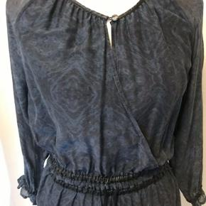Kjole i silke med flot knap foran, der skinner knallert regnbuens farver. Udskæringen falder flot. Elastik og bindebånd i taljen.