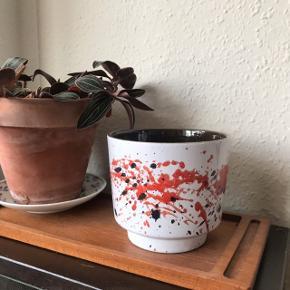 Smuk tysk urtepotteskjuler i hvid, rød og sort 💥 fed retro skjuler, der måler ca. 12 cm i diameter, og 10,5 cm i højden. Rigtig fin stand, har dog en mini revne, se sidste billede 🌹  Bemærk - afhentes ved Harald Jensens plads eller sendes med dao. Bytter ikke 🌸  💫  Urtepotte urte potte skjuler hvid råd sort west Germany tysk wg