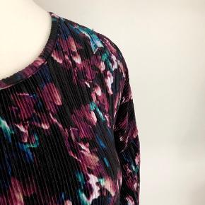 Cha Cha plisseret kjole med lange ærmer i farverne bordeaux, sort, hvid blå og grøn. Længde fra skulder er 100 cm. Brystmålet går fra 116-140 cm. Taljen måler fra 104-130 cm. Fremstillet af polyester, men der er meget stretch i. Bærer ikke præg af brug.