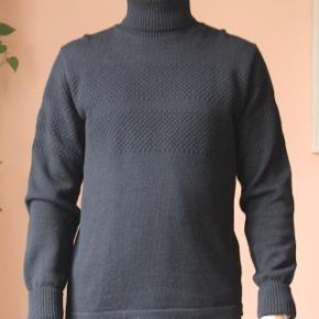 Klassisk Mads Nørgaard højhalset uldsweater. 100% ny dansk uld. Aldrig rigtig brugt da den ikke er min stil og fremstår derfor næsten som ny. Er ikke vasket men renset da det som sagt er 100% uld. Super til vintermånedernes kolde vejr :) Jeg er 188 høj, vejer 83 kg. og er ganske normal af bygning.  Kan afhentes i Aarhus C eller sendes på købers regning! Alt tøjet kommer nyvasket!