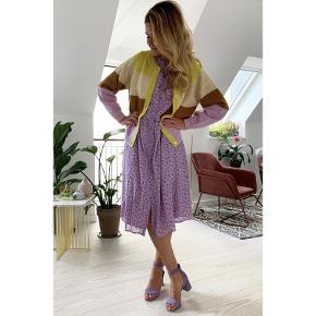 Lollys Laundry kjole, der i sandhed er så smuk, at den vil blive din favorit henover sommeren. Aliya kjolen kommer i en lyselilla farve med små, fine blomster i en lys orange og lilla farve.  Kjolen har korte ærmer, knapper langs forsiden og pasformen er løs med skæring i taljen. Kjolen har en tynd foring, der gør den perfekt til de lune aftner på altanen, eller hvis du skal til havefest. Ydre: 100% polyester  For: 100% viskose Str. XS, men en løs kjole så en str. S + lille M vil også kunne passe den, kjolen er helt ny.