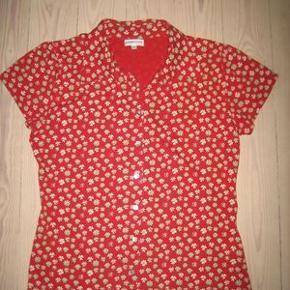 100 % NY: Lækker bluse /skjorte fra Peppercorn med lidt strech i stoffet (bomuld/polyester). Rød med små blomster. Blusen knappes med søde firkantede perlemorsknapper.   Brystvidde: 52 cm x 2 Længde: 63 cm  Ingen byt, og prisen er fast.