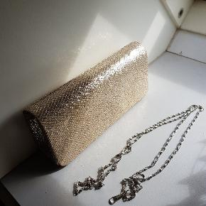 Festtasken med guld glitter! Den har aftagelig kæde så du kan have den over skulder eller som clutch. Den drysser ikke og hænger ikke fast i kjolen - hvilket har været et stort plus i min bog. Kan afhentes i Sønderris eller sendes på købers regning.