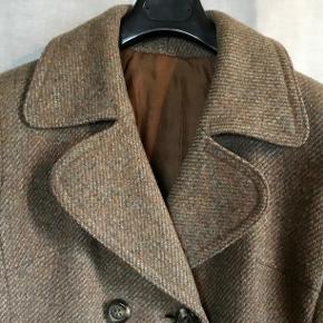 Fra DANKI : Dansk produceret. 100 % uld frakke i klassisk snit. Brugt sparsomt og yderst velholdt. Knaplukning foran. Helforet. To skrålommer. Med indsnit og figursyet. Klassisk krave og bredt bånd ved ærmeafslutning. Der står ingen størrelse i, men passer str. 38-40. Sender gerne på købers regning.