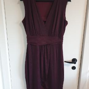 Flot tætsiddende lilla kjole med sort glimmer. Brugt en gang.   Kan afhentes i Aarhus omkring Storcenter Nord eller sendes for købers regning.  Se gerne mine andre annoncer.