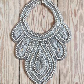"""Fantastisk vintage krave/halskæde/smykke. Fra starten af det 20. århundrede, dvs. den edwardianske periode. Et unika og virkelig virkelig smuk. Den er besat med flere forskellige typer af perler: hvide saltvandsperler (ikke ægte), små aflange røgfarvede perler der omkranser de hvide, samt et hav af bittesmå klare perler, der udfylder resten af kraven. I midten af hver """"bue"""", sidder der store sølvfarvede pailletter. Det er et fantastisk stykke håndværk og har formentlig været brugt til at pynte en kjole. Der er ikke nogen lukkemekanisme, så hvis man vil bruge den, skal man sætte en sikkerhedsnål eller evt. sy trykknapper i.   Der er en række mangler og brugsspor, alderen på smykket taget i betragtning. Der mangler et par enkelte hvide perler - så vidt jeg kan se, kun omkring tre, hvis man virkelig kigger efter. I bue nr. to fra venstre er den nederste paillet revnet. I den midterste store bue, mangler sølvpailletten helt. Dette vil en ferm hånd sagtens kunne reparere. Kraven fremstår derudover intakt. Et stykke antik historie."""