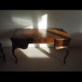 Jeg sælger dette skrivebord, som er et gammelt skrivebord i delvist massivt egetræ. Skrivebordet er i stilen nyrenæssance fra cirka 1930-1948.  Bordet er et meget fint håndværk og har nogle smukke udskæringer. Der er i alt 5 skuffer.   Da skrivebordet godt kan trænge til en renovering i form af en overfladebehandling, har jeg valgt at slå en stor del af prisen af.   Bordet skal afhentes i Horsens.