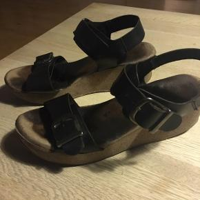 Sandaler m/ kilehæl - sort læder med kork kilehæl. Størrelse: 39 De er brugte, men de er stadig rigtig fine. De skal nok have en ny sål på sigt.  Nypris: 799,-