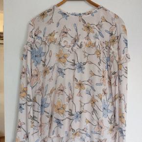 """Den smukkeste bluse med flæser ved bærestykket,  ærmer og i hals. Med """"guldknapper"""" ligeledes ved ærmer og i hals."""