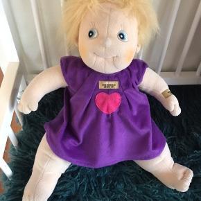 Rubens Barn - Rubens dukke - Original Ida   Rubens Dukke Original Ida er en sød og empatisk dukke, som er håndlavet i blød polyester-fleece.  Hendes krop er fyldt med granulat, som giver hende en god tyngde i numsen. En ting der kendetegner Rubens Dukkerne.  Originale Ida har en flot lilla kjole på. Hun kan grundet hendes størrelse også godt passe almindelig babytøj.   Alle dukkerne fra Rubens Barn har det sødeste ansigt. Med deres uskyldige øjne, rødblussede kinder, lange øjenvipper og fregner er de ikke til at stå for.  Dukkerne er håndlavet og derfor har flotte unikke detaljer. De meget velegnet til at stimulere barnests fantasi, berøring og leg. De er super dejlige at kramme - og kontakten er med til at motivere barnets indlæringsevne.  De er endvidere også meget velegnet til demente voksne.  Materiale:Blød polyester-fleece Mål: H. 50 cm Vægt: 1 kg. Lys hudfarve, lilla kjole Alder: 0 + Selve dukken kan vaskes ved 30 grader i vaskemaskine. Tøjet skal vaskes i hånden.  Der står navn på vaskemærket.   Købspris 579,-