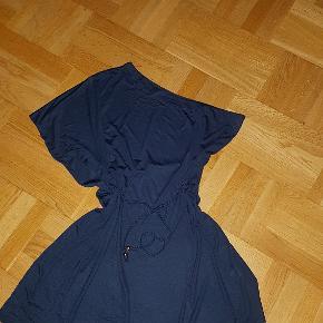 Asymmetrisk kjole med kort ærme på højre side og ærmeløs på venstre side. Kjolen har et flot flettet bælte med en guldperle i hver ende. Kjolen er i et blødt let stof, der smyger sig og falder flot.
