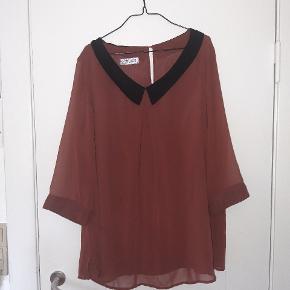 Brugt og elsket tunika/bluse, men i god stand, meget lidt tegn på slid. En flot rust rød farve med boatneck line og fin sort krave.
