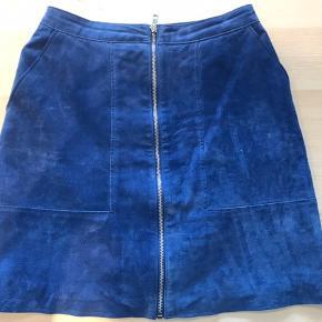 Super lækker ruskindsnederdel - blå med for indeni - den kan ikke vaskes - skal bare tørres af med en våd klud. Den kan lynes helt op så den er nem at få af og på.