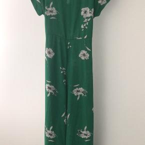 Super fed buksedragt i grøn med fine hvide blomster den er aldrig blevet brugt så der er ingen slid på den