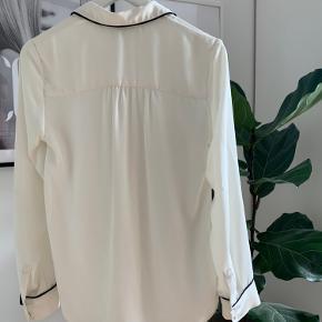 Fin hvis skjorte med sorte detaljer fra H&M. Den blev desværre hurtigt for lille til mig, så er derfor brugt få gange. Lækker i kvaliteten og krøller ikke efter vask.