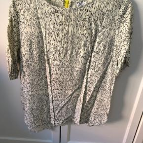 Let skjorte med sorte detaljer og gul lynlås i nakken.