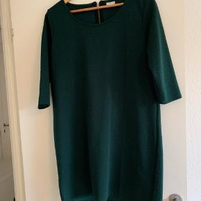 Mørkegrøn kjole med lynlås i ryggen. Farven er som på billede 1 og 3. Sender gerne med DAO.
