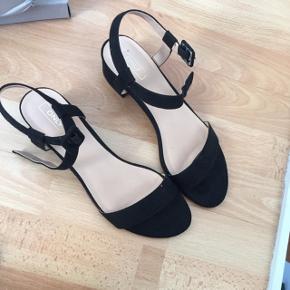 """Sorte sandaler med lille hæl. Mangler """"metal-tingen"""" i den ene spænde (se billede). Det skal man selv have sat i. Afhentes i Aarhus."""