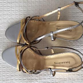 Elegante Italienske guld sandaler med kilehæl og tre-farvede remme over vristen. Hælen er 8 cm.  Guld sandal med kilehæl Farve: Guld Oprindelig købspris: 1098 kr.