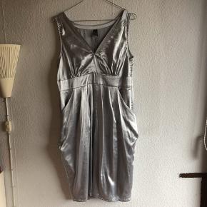 Brugt 1 gang. Sølv kjole med fine detaljer. Lynlås i siden. Satin look  BYD gerne, sender via dao på købers regning. Kommer fra et røgfrit hjem.