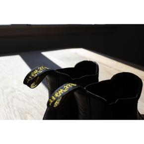 Læder Chelsea boots - Enkle  - Ægte læder - Behagelig at gå i  - Nypris: 1300kr - Har et par skræmmer på snuden(se billede 3)  -Indvendig kan man se, at de er brugt(skriv for flere billeder)    Pasform: - Gode hvis man ønsker at være højere, da de ha ren hæl(den er ikke feminin)  -Passer en str. 36  Styling: - Passer godt til straight leg sorte cowboybukser  - Passer godt til bukser der går over anklen, så man kan se hele støvlen  - Klæder det meste tøj, da de er sorte og simple