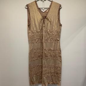 Der er en lille plet på i kanten på kjolen. Har ikke haft vasket kjolen og forsøgt at få pletten væk, da den aldrig har været brugt.