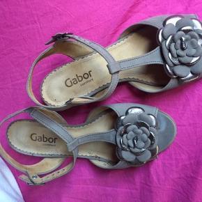 Brand: Gabor comfort Varetype: fin sandal med blomst Størrelse: 5 H (5 = 38) Farve: brun / dådyr / mulvarp Oprindelig købspris: 900 kr.  Sød og fin sandal i en str. 5 H, indvendig længde ca. 24½ cm.  Stødabsorberende pude indbygget i sål....   Materiale nubuck. Fin sløjfe foran på sandalen. Hælhøjde ca, 4 cm.  Sandalen er meget velholdt og brugt ganske få gange.  Sendes med DAO/GLS.