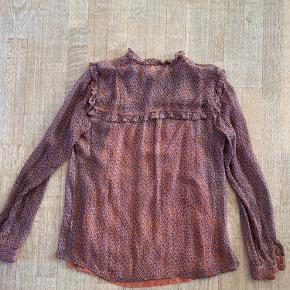 Super fin silkeskjorte fra Custommade i brun/orange med denimblåt blad-mønster og blondekant.  Skjorten har en tilhørende under-top, som kan knappes af og på. Materialet er 93% silke og 7% lurex. Jeg har en matchende nederdel i en af de andre annoncer, og de to dele er super flotte sammen/som sæt.