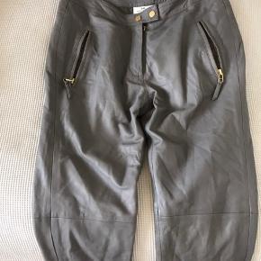 Lækreste lammeskinds læderbukser. Tætsiddende model med skrålommer og lynlåse i benene.  Virkelig flot grå farve.  Guld detaljer.  Nypris 2700. Brugt få gange.  Livvidden er ca 40 x 2. Køber betaler Porto.