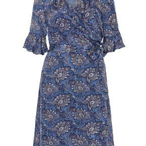 Claire Woman Slå-om-kjole med bindebånd i taljen. 3/4-ærmer med flæsekanter og en flæsekant rundt om halskanten som krave. Kjolen kan knappes med en lille trykknap over brystet. Længde bag på: 108 - under knæet. Underkjole med tynde, justerbare stropper. 100% Viskose Fejlkøb.  De to første billeder er fra Claire Womans hjemmeside.