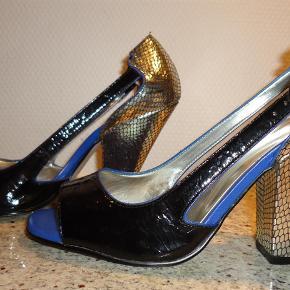 Varetype: Heels med åbne sider og peeptoe Farve: Blå, sort og sølv Oprindelig købspris: 900 kr.  Super fede heels fra Topshop. Peeptoe og åben i siderne. Blå bund foran, sort lak på forfoden, sølv hæl og hælkappe.  Købt her på TS og sælger oplyst de kun har været på to gange. Aldrig selv fået dem i brug - de er desværre for høje til mig efter jeg har fået en ankelskade.