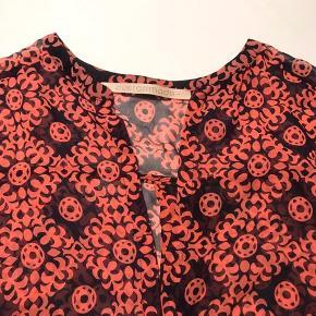 Silketop i løst fit med 3/4 lange ærmer. Er 5 cm kortere i front end bagpå. Kan vaskes.