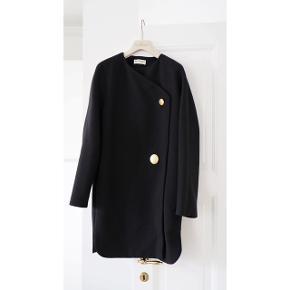 """Smuk uld frakke fra Balenciaga.   Klassisk med et moderne tvist med den asymetriske lukning.   Str 42 som svarer til large. Bruger normalt small, så den fitter """"oversize"""", hvis man kan lide det look.   Næsten ikke brugt og fremstår derfor rigtig flot.   Nypris 12.000kr. Købt i Firenze.  Mp 5.500kr"""