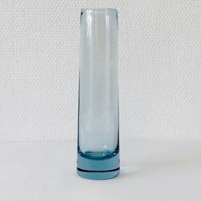 Vase fra Holmegaards Akva serie designet af Per Lütken. Vasen er cylindrisk og let konisk. Signeret: Holmegaard, PL, 220277 Højde: 24 cm Diameter: 6,4 cm