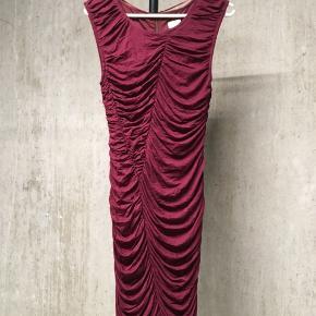 Brugt 1 gang - derfor i perfekt stand.  Str. 36.  Flot draperet kjole, der sidder tæt til kroppen. Lynlås bagpå.