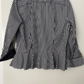 """Duper smuk og feminin skjorte med en """"flæse"""" forneden og kontrast farve på ærmeombukkene. Str. 10/m - købt i New York. Aldrig brugt. Længde: 60 cm"""