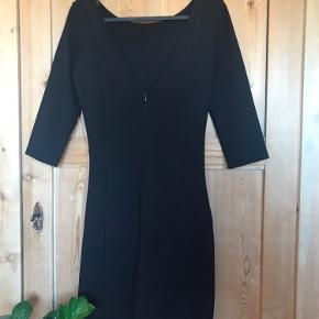 Stram kjole med fin crapped detalje foran i den ene side og 3/4 ærmer.  Har underkjole og er ret tyk i stoffet. Dyb v-ryg med skjult lynlås.
